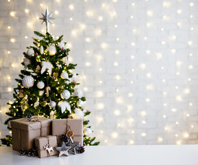 christmas and new year concept - beige gift boxes near decorated christmas tree and copy space over...
