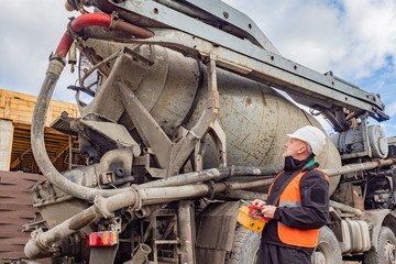 A man in a white helmet holding a remote control supply of cement.Worker directs the unloading of cement. Cement is fed from the mixer. Remote control concrete mixer. Man controls the flow of concrete