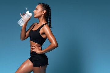 sexy tanned thirsty girl enjoying drinking fresh water. close up side view photo. isolated blue...