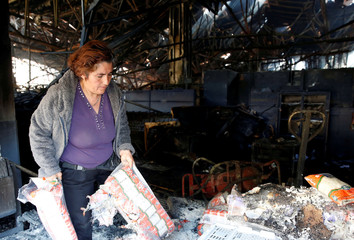 A woman takes bags of rice inside a burnt and looted supermarket one day after a protest against the government in Valparaiso
