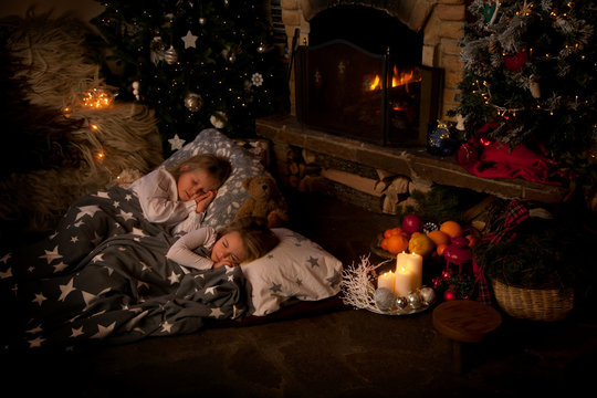 Two children sleeping in front of the fireplace on Christmas Eve