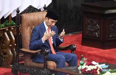 Indonesian President Joko Widodo gestures as he prays after taking his oath during his inauguration and a swearing-in ceremony of Joko Widodo and his New Vice President Ma'ruf Amin, at the House of Representatives building in Jakarta