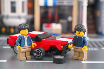 Tambov, Russian Federation - October 18, 2019 Two lego minifigures changing front wheel of a muscle car.