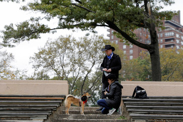 Diane Leighton and Carl Kazmirek attempt to photograph their dog Nori, a Shiba Inu, dressed as a cowboy, at the Tompkins Square Halloween Dog Parade in Manhattan, New York City