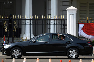 Indonesian President Joko Widodo waves from a car, on his way to his inauguration and swearing-in ceremony for the second term, in Jakarta