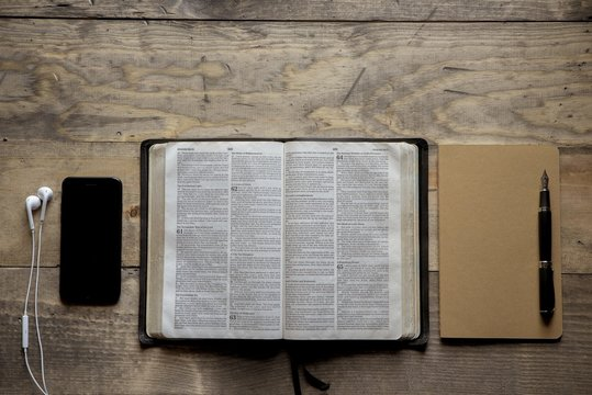 Overhead shot of opened bible in the middle of a notebook and a smartphone on a wooden surface