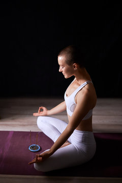 Short-haired caucasian woman sit in lotus pose and meditate. Yoga meditation. Black background