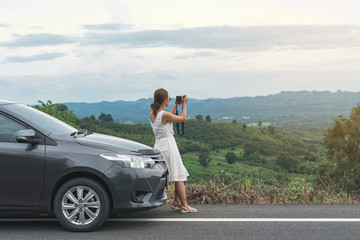 Young woman traveler taking a photo on mountain with car on roadtrip, Summer vacation