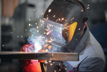 Welder is welding a metal frame.