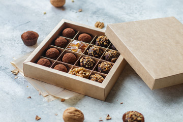 Set of chocolate truffles with nuts and cocoa. Tasty round candy. A delicious gift in a Kraft paper box. Holiday concept. Selective focus