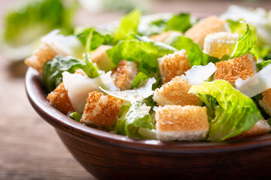 Bowl of caesar salad with cheese and croutons