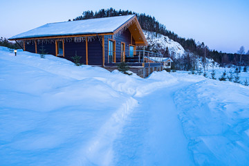 Wooden cottage. Two-story house on a hill. Garlands on the roof of the house. Rent a cottage for the new year. Winter holidays in the countryside. Snow near the house. Vacations far from the city.