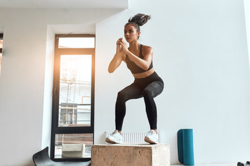 Beautiful sporty woman in sportswear jumping on wooden box in gym. Training, cross fit, sport