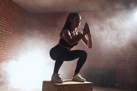 Slim woman jumping on wooden fit box, performing squats. Steam back, brickwall background. Crossfit, bodybuilding, sport concept
