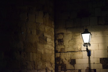 light on a light brown stone wall at night Fotomurales