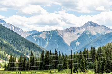View of mountain peaks and power cables lines near Ouray, Colorado with San Juan rocky mountains in summer from Million Dollar Highway