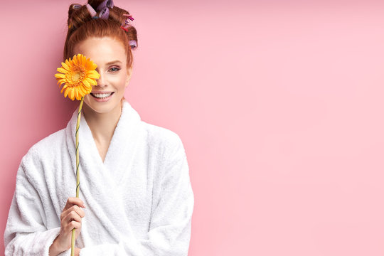 Young smiling woman holding daisy yellow flower isolated over pink background. Female wearing white bathrobe, curlers on hair after shower. Natural beauty