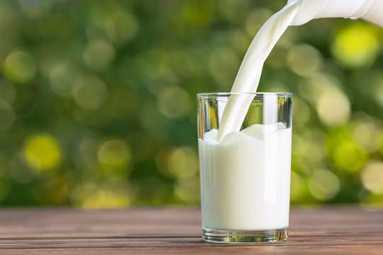 milk from jug pouring into glass