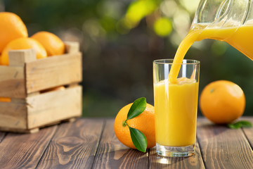 Foto op Canvas Sap orange juice pouring in glass