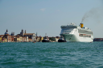 Italian luxury cruise ship Costa Victoria cruising the Giudecca Canal with tug boats towards the cruise terminal in the port of Venice Venezia with skyline and traffic on waterway