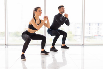 Deep squat. Fitness couple in sportswear doing squat exercises at gym