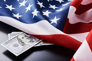 USA national flag and currency usd money banknotes on a dark background. Business and finance concept