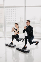 Fit couple working out make squats together at gym