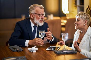 Senior couple spend time in restaurant, speaking, use modern technologies - laptop, tablet, IQOS. Elegant grey-haired man in tuxedo, woman in white blazer