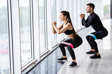 Attractive couple exercising with a resistance band in gym