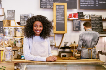 Smiling young African American entrepreneur working behind her cafe counter