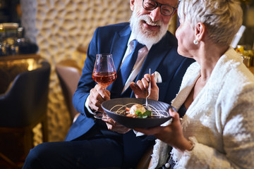 Caucasian man in suit and eyeglasses, beautiful woman in white elegant blazer enjoy meal in attractive place. Sweet dessert and glass of champagne. Love in the air