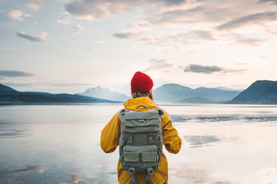 Man tourist wearing yellow jacket and backpack standing in front of fjord. Back view of alone hiker standing by the coast sea among mountains