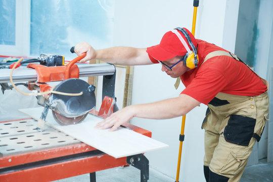 Tiler cutting tile on wet saw machine