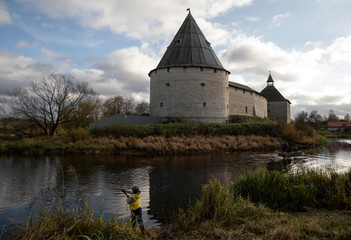 A boy fishes in front of the fortress of the town of Staraya Ladoga