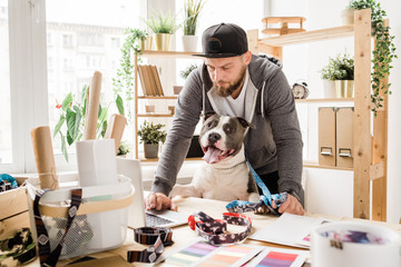 Young serious designer in casualwear bending over laptop with pet