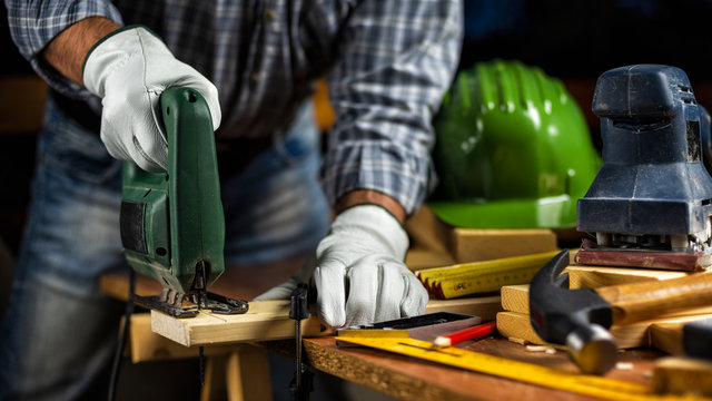 Adult carpenter craftsman wears protective leather gloves, with electric saw working on cutting a wooden table. Construction industry, housework do it yourself. Stock photography.