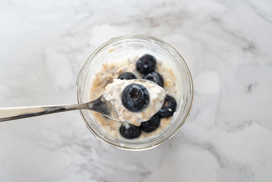 Overnight oats with chia seeds, blueberries and yogurt, on a white marble background.