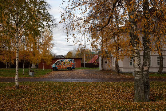 A minibus is seen parked next to autumn coloured trees in the town of Staraya Ladoga