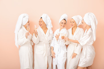 Beautiful young women in bathrobes drinking champagne on color background