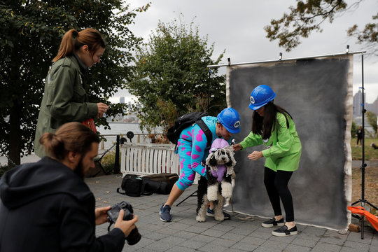 People prepare to pose in a makeshift photo studio in the backstage area at the Tompkins Square Halloween Dog Parade in Manhattan, New York City