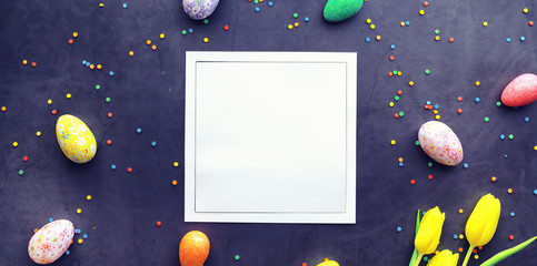 Easter background on black stone. Multicolored eggs and sweet.