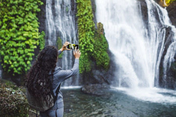 Woman taking picture of waterfall Banyumala in Bali. Long curly brunette hair, backpack. Travel concept.