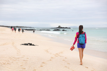 Galapagos Islands - woman on cruise ship tour visiting Playa las Bachas Beach on Santa Cruz Island. Woman walking barefoot in sand enjoying pristine nature landscape ecotourism