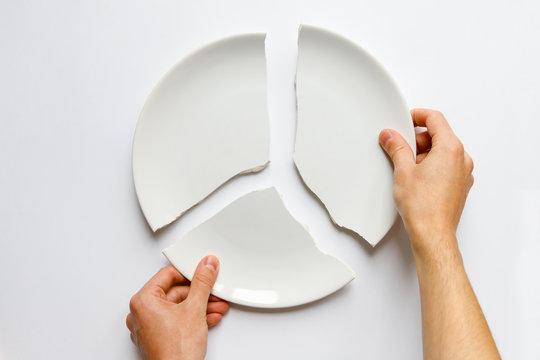 Top view of man hands holding a broken white plate. Metaphor for divorce, relationships, friendships, crack in marriage. Love is gone. Isolated on white background.