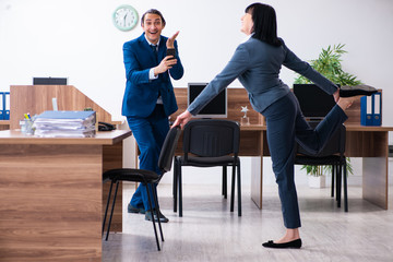 Two employees doing sport exercises in the office