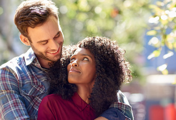 Diverse young couple standing outside looking into each other's eyes