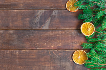 Christmas background on brown wooden table with pine branches and dry orange slices. Image with copy space, top view.