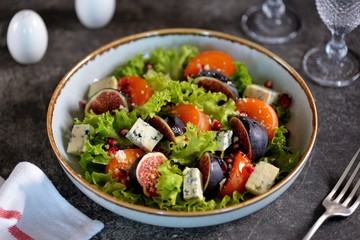 Healthy salad of persimmons, figs, blue cheese, pomegranate seeds, parmesan, lettuce and olive oil.