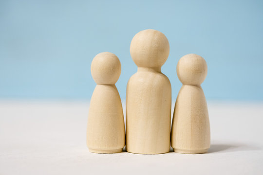 Wooden figures of man with two woman or adult with two children.