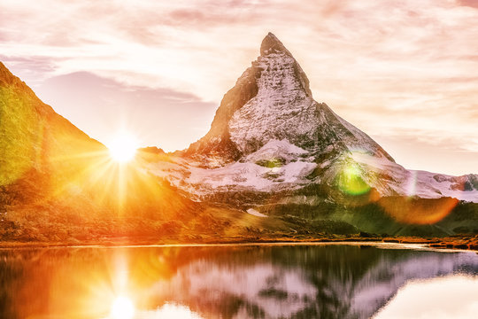 Matterhorn mountain peak, Switzerland, seasonal autumnal scene. Epic sunset view on Matterhorn mountain peak in Switzerland over Riffelsee lake. Sun glowing during sunset. Swiss mountain landscape.